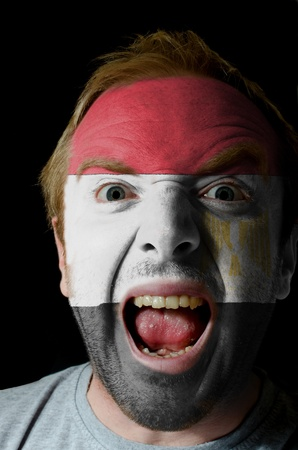 whose: Low key portrait of an angry man whose face is painted in colors of egypt flag