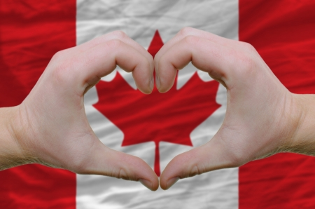 Gesture made by hands showing symbol of heart and love over canada flag photo