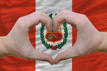 Gesture made by hands showing symbol of heart and love over peru flag photo