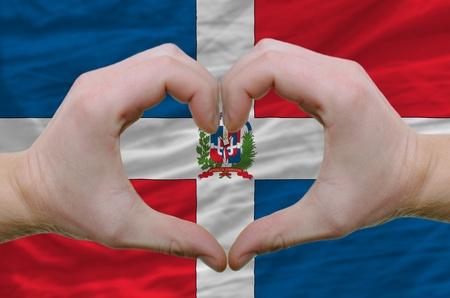 republic of dominican: Gesture made by hands showing symbol of heart and love over dominican flag