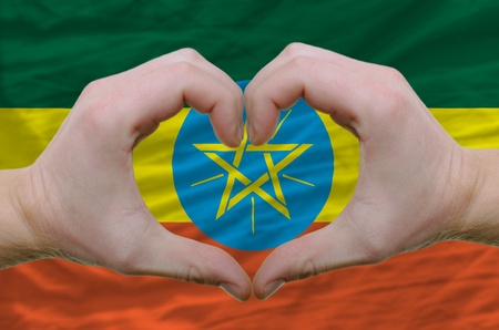 Gesture made by hands showing symbol of heart and love over ethiopia flag photo