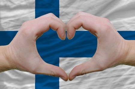 Gesture made by hands showing symbol of heart and love over finland flag photo
