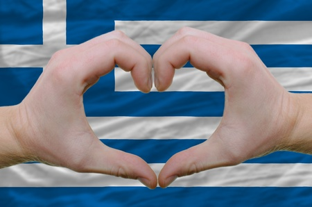 Gesture made by hands showing symbol of heart and love over greece flag photo