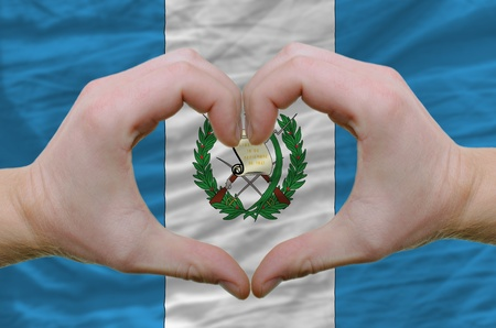 Gesture made by hands showing symbol of heart and love over guatemala flag photo