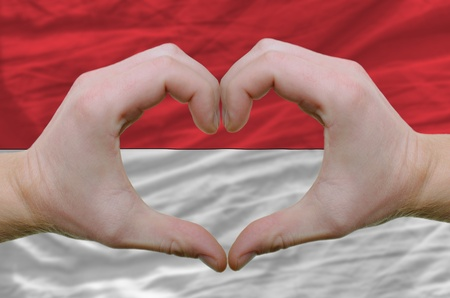 Gesture made by hands showing symbol of heart and love over indonesia flag