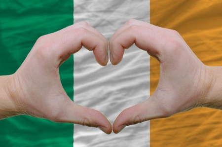 Gesture made by hands showing symbol of heart and love over ireland flag photo