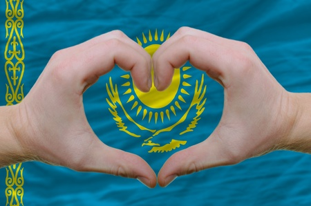 Gesture made by hands showing symbol of heart and love over kazakstan flag photo