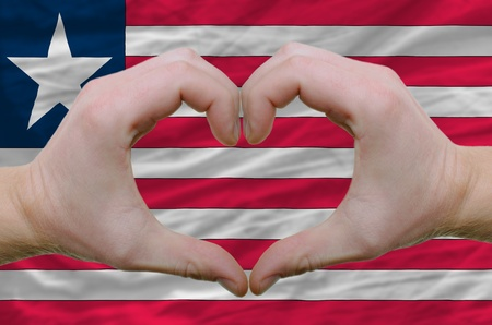 Gesture made by hands showing symbol of heart and love over liberia flag photo