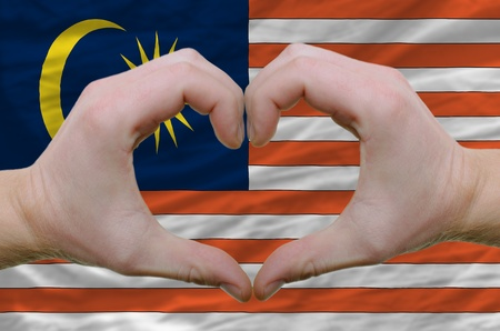 Gesture made by hands showing symbol of heart and love over malaysia flag photo