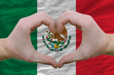 Gesture made by hands showing symbol of heart and love over mexico flag photo