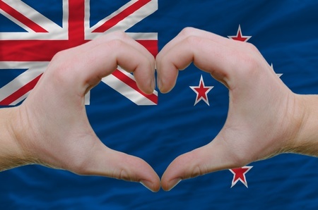 Gesture made by hands showing symbol of heart and love over new zealand flag photo