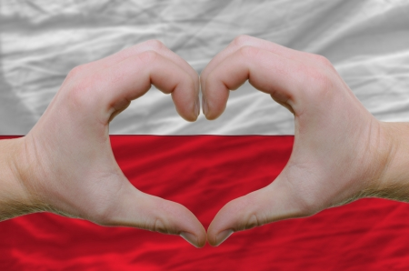 Gesture made by hands showing symbol of heart and love over poland flag photo