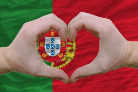 Gesture made by hands showing symbol of heart and love over portugal flag photo