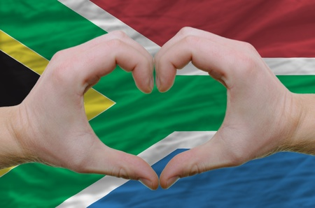 Gesture made by hands showing symbol of heart and love over soth african flag photo