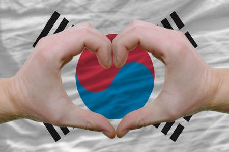 Gesture made by hands showing symbol of heart and love over south korean flag photo