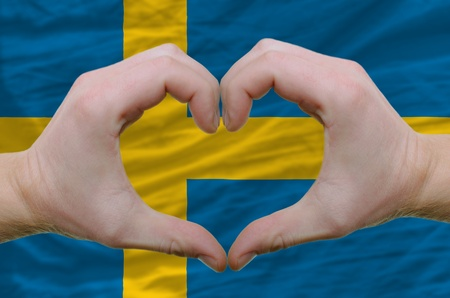 Gesture made by hands showing symbol of heart and love over sweden flag photo
