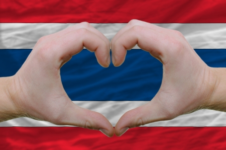 Gesture made by hands showing symbol of heart and love over thailand flag photo