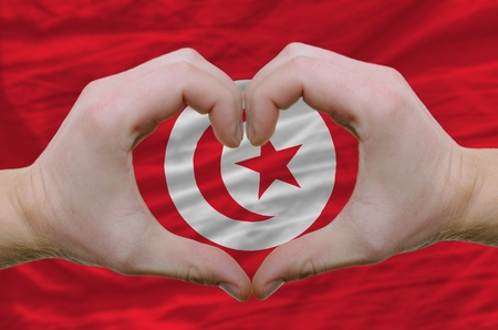 nationalist: Gesture made by hands showing symbol of heart and love over tunisia flag Stock Photo