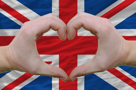 britannia: Gesture made by hands showing symbol of heart and love over united kingdom flag