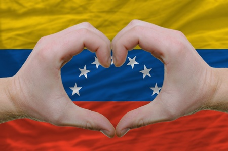 Gesture made by hands showing symbol of heart and love over venezuela flag photo