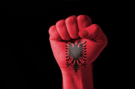 albanian: Low key picture of a fist painted in colors of albania flag Stock Photo