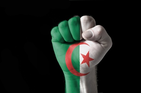 Low key picture of a fist painted in colors of algeria flag photo