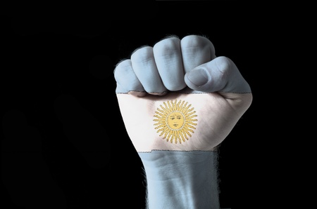 Low key picture of a fist painted in colors of argentina flag Stock Photo