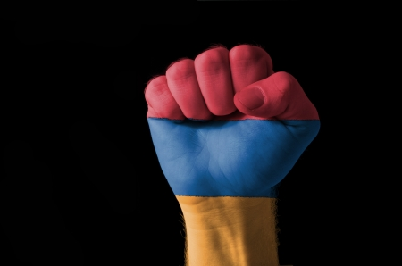 Low key picture of a fist painted in colors of armenia flag photo