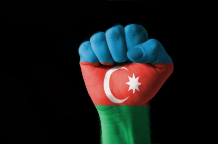 Low key picture of a fist painted in colors of azerbaijan flag
