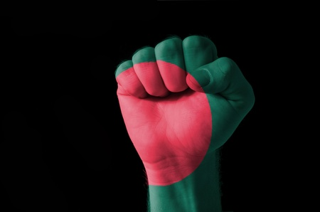 Low key picture of a fist painted in colors of bangladesh flag photo