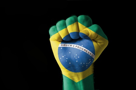 brasil: Low key picture of a fist painted in colors of brazil flag Stock Photo