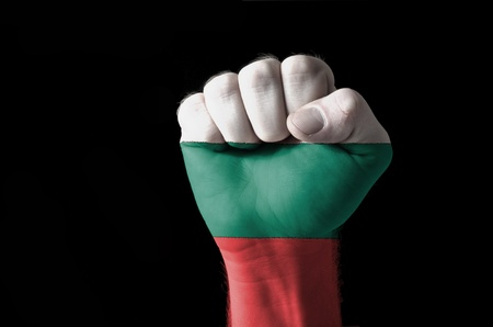 Low key picture of a fist painted in colors of bulgaria flag photo