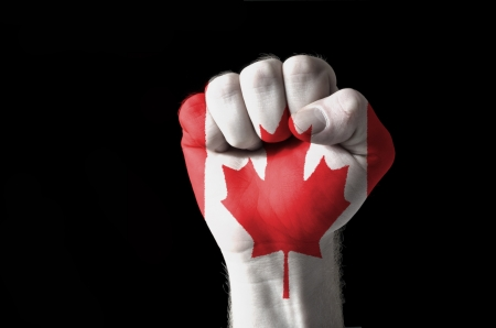 canada: Low key picture of a fist painted in colors of canada flag Stock Photo