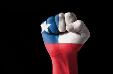 Low key picture of a fist painted in colors of chile flag photo