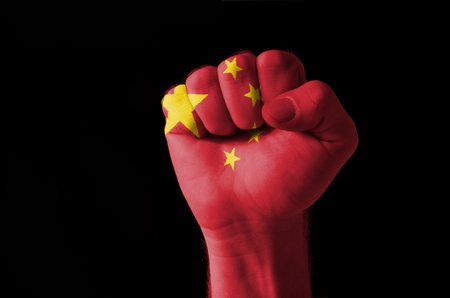 Low key picture of a fist painted in colors of china flag photo