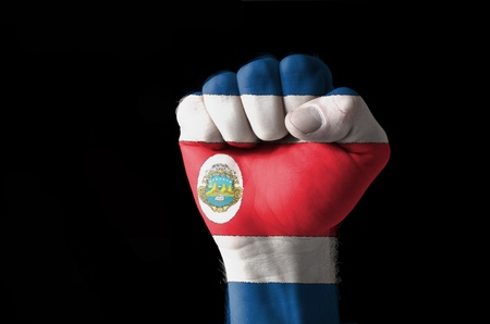 costa rican: Low key picture of a fist painted in colors of costarica flag