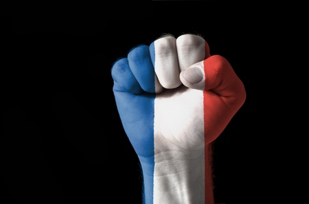 Low key picture of a fist painted in colors of france flag photo