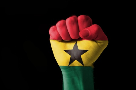 aggressor: Low key picture of a fist painted in colors of ghana flag Stock Photo