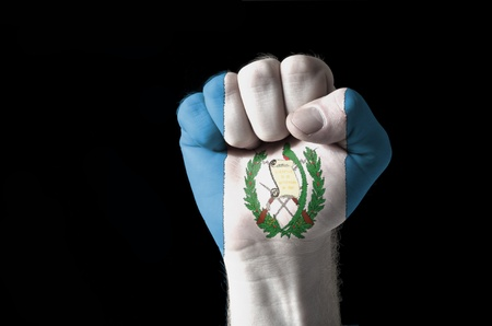 aggressor: Low key picture of a fist painted in colors of guatemala flag Stock Photo