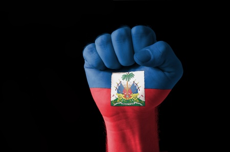 haitian: Low key picture of a fist painted in colors of haiti flag Stock Photo