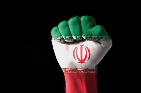 Low key picture of a fist painted in colors of iran flag