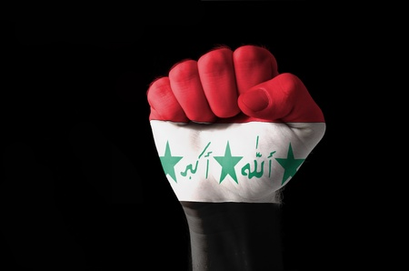 Low key picture of a fist painted in colors of iraq flag photo