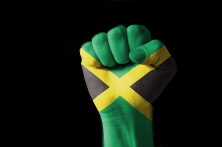 jamaican: Low key picture of a fist painted in colors of jamaica flag Stock Photo