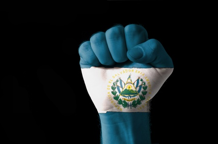 el salvador: Low key picture of a fist painted in colors of san salvador flag