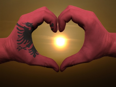albanian: Gesture made by albania flag colored hands showing symbol of heart and love during sunrise