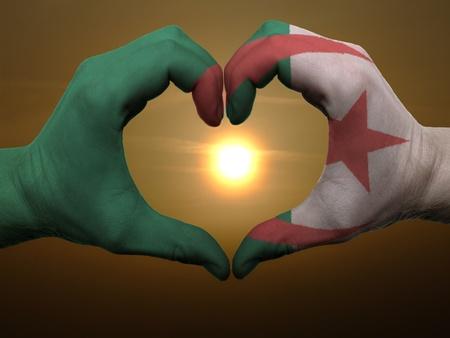 Algierski: Gest wykonany przez Algierię bandery rękach kolorowych przedstawiających symbol serca i miłości podczas wschodu słońca