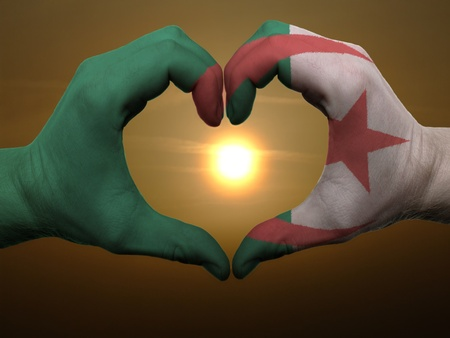 afghanistan flag: Gesture made by algeria flag colored hands showing symbol of heart and love during sunrise