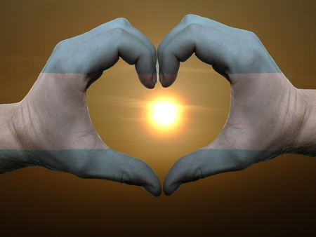 argentina flag: Gesture made by argentina flag colored hands showing symbol of heart and love during sunrise Stock Photo