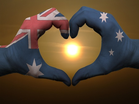 australian flag: Gesture made by australia flag colored hands showing symbol of heart and love during sunrise