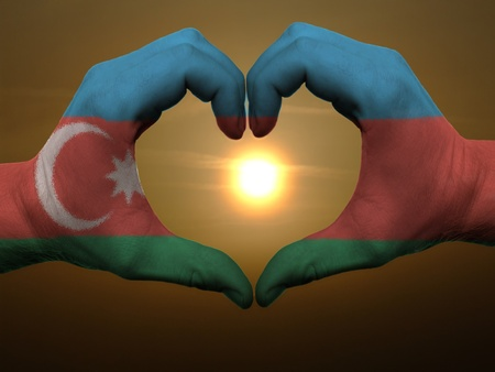 azerbaijanian: Gesture made by azerbaijan flag colored hands showing symbol of heart and love during sunrise